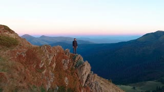 The man standing on the rock with a beautiful landscape