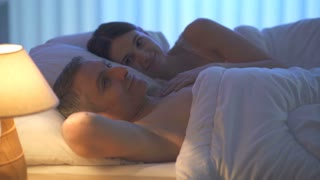 The man talk with a woman on the bed. Evening night time