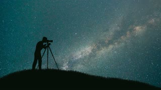 The man with a camera stand on the mountain against a sky with stars. time lapse