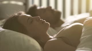 The nervous woman lay near the man on the bed
