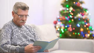 The pensioner read a book and smile near the christmas tree