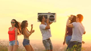 The people with a boom box dancing on the sunrise background. slow motion