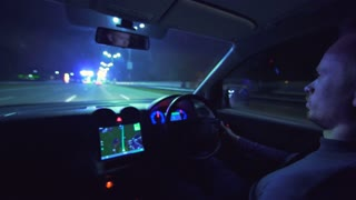 The serious man drive a car on a night autobahn. left side traffic. inside view, real time capture
