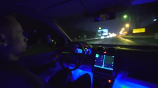 The serious man drive a car on the road. evening night time. inside view, real time capture