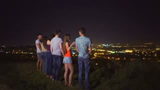 The six people stand on the background of the city lights. evening night time