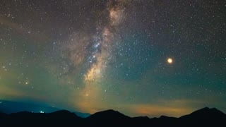 The sky with stars above mountains. time lapse