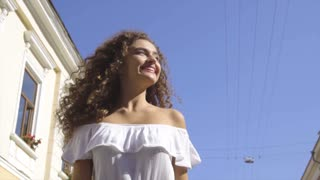 The smiling woman walking outdoor. slow motion
