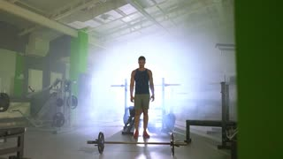 The sportsman lifting a burbell in the fitness center. slow motion