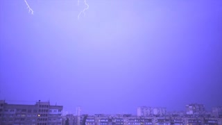 The thunderstorm with lightning above a night city. slow motion