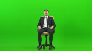 The tired businessman sitting on the office chair on the green background