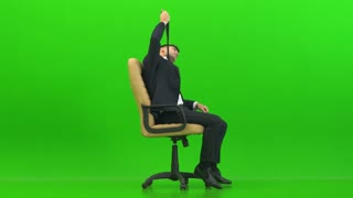 The tired man sitting on the office chair on the green background