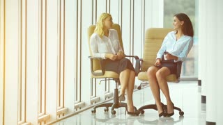 The two business ladies sit and talk in the office hall