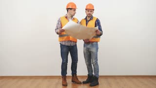The two engineers with a drawing talk on the white background