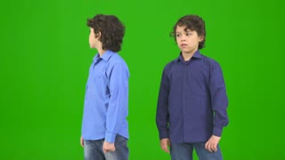 The two funny twin kids gesture on the green background
