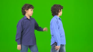 The two happy twin kids gesture on the green background