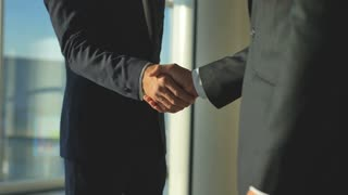 The two men handshake in the office. slow motion