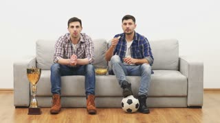 The two men watch football on the sofa and eat chips