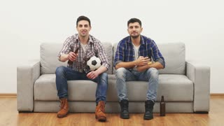 The two men watching a football on the sofa on the white wall background