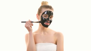 The woman applying a black face mask on the white background