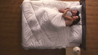The woman hug a man in the bed. view from above