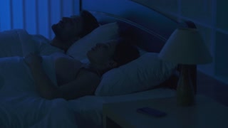 The woman lay on the bed and phone near the man. night time