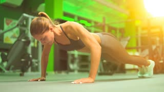 The woman push up from the floor in a sport club