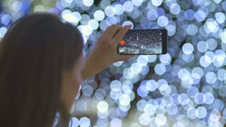 The woman with a smartphone shot bright lights. Real time capture