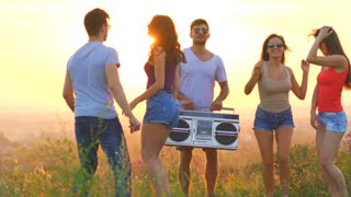 The young people with a boom box dancing on a sunset background. slow motion