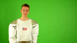 astronaut points at American flag on his helmet - green screen