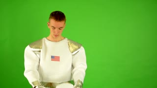 astronaut puts on helmet and looks into camera - green screen