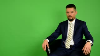 business man sits and talks to camera (interview) - green screen - studio