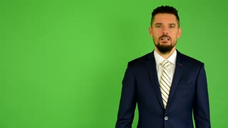 business man talks to camera (interview) - green screen - studio