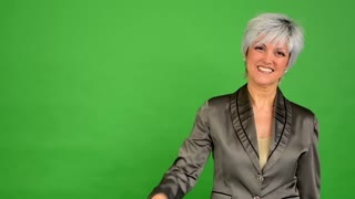 business middle aged woman points to the camera - green screen - studio