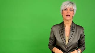 business middle aged woman talks to camera (interview) - green screen - studio