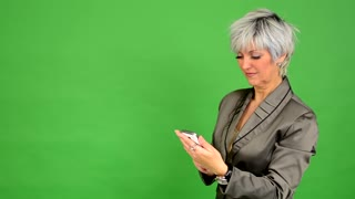 business middle aged woman works on phone and smiles - green screen - studio