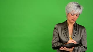business middle aged woman writes to paper and smiles to camera - green screen