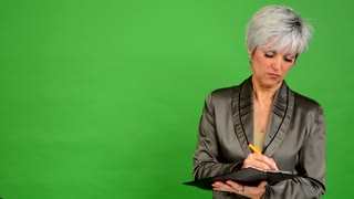 business middle aged woman writes to paper (serious face) - green screen