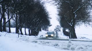 Car on snowy road go through the alley