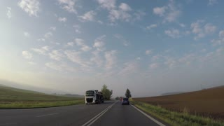 car rides on the road through the grassland surrounded by large fields