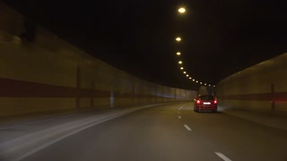Cars departue from tunnel and go on road at night