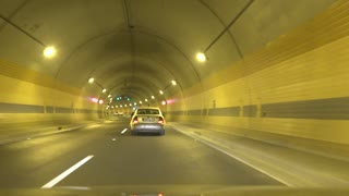 Cars go on road in tunnel
