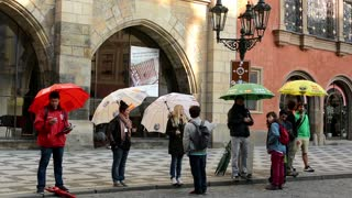 city - urban street - tour guides - people with umbrella