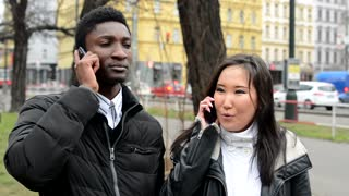 Happy couple phone - black man and asian woman - urban street with cars - city