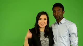 Happy couple show thumb on agreement - black man and asian woman - green screen