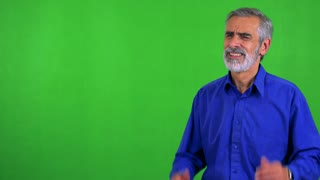 old senior man is afraid (man covers his ears with hands) - green screen
