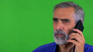 old senior man phones with smartphone - green screen - studio - closeup