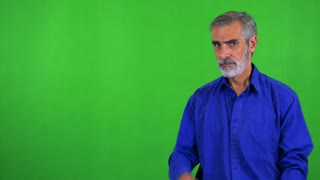 old senior man points on watch (show time) - green screen - studio
