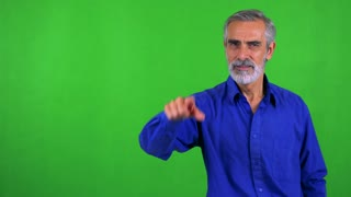 old senior man points to camera with finger - green screen - studio