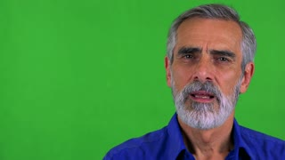 old senior man talks to camera - green screen - studio - closeup