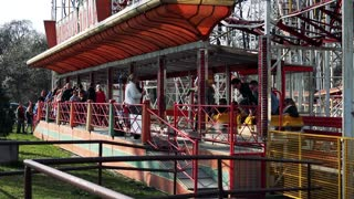 People get off from seats of  roller-coaster in funfair